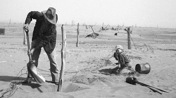A Dust Bowl farmer digs out a fence post to keep it from being buried under drifting sand in Cimarron County, Okla., in 1936. © Arthur Rothstein/ Library of Congress from NPR